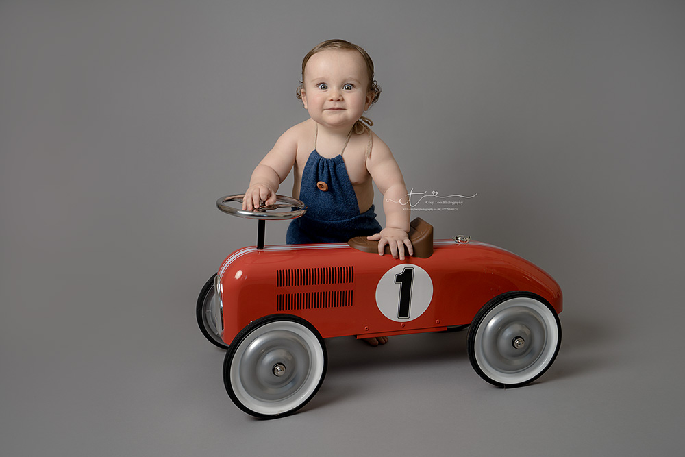 Baby boys standing by red car smiling at first birthday photo shoot in Crawley