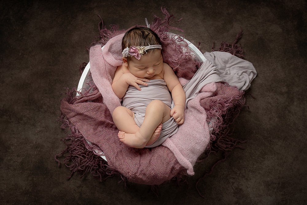 Newborn baby girl sleeping wrapped in in white bowl