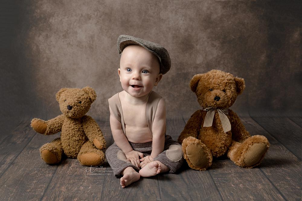 Baby boy wearing braces and flat cap between two teddies