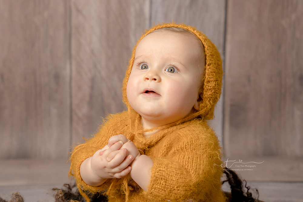 baby boy clasping hands in mustard bonnet photographed by East Grinstead baby photographer