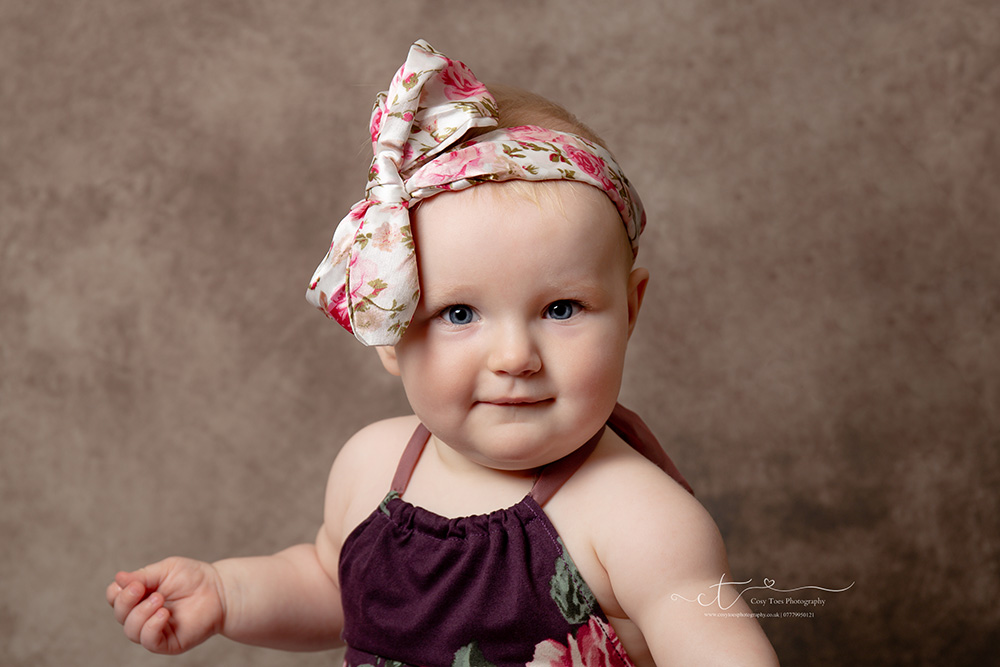 baby girl 8 months old with large bow on her head looking mischievous at her photoshoot in Redhill