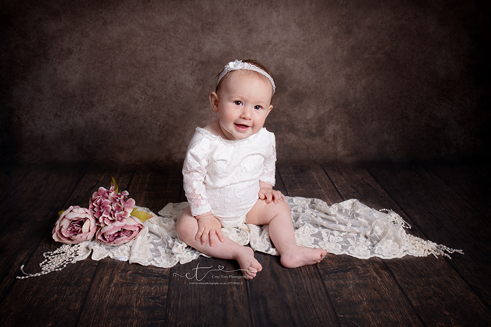 Baby girl 7 months old sitting on lace wrap smiling at her baby photoshoot in Eastbourne