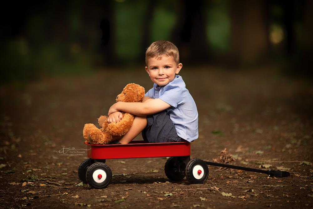little boy sitting on a red cart cuddling teddy at childrens photo shoot Crawley