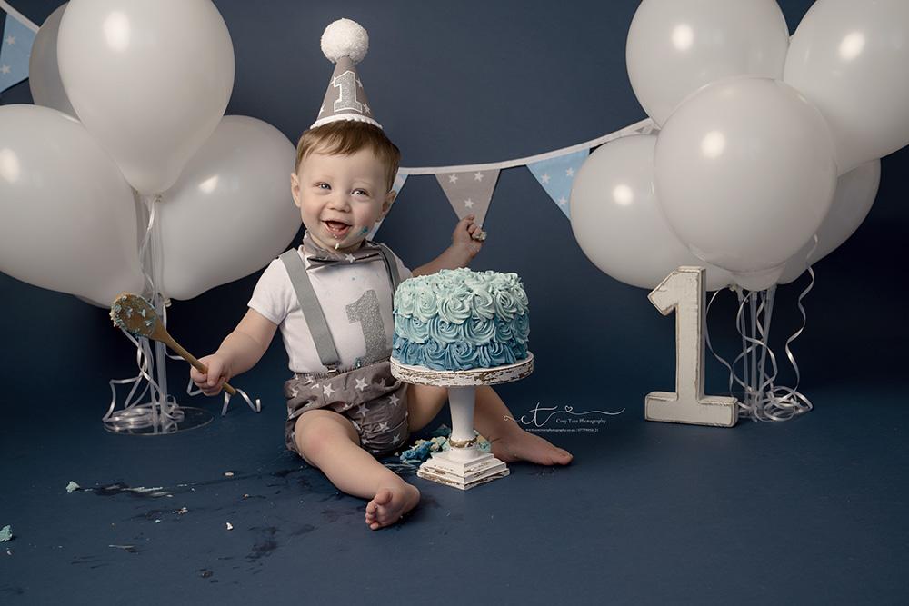 Baby boy laughing on dark blue cake smash set by Kent baby photographer