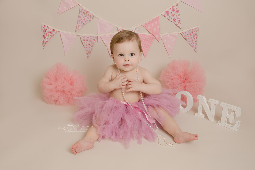 Baby girl wearing bead necklace and tutu in East Grinstead