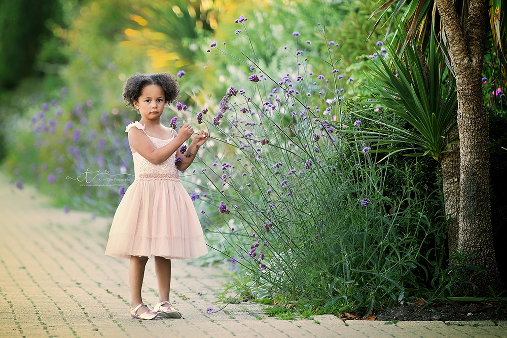 Little girl in summer dress next to tall flowers