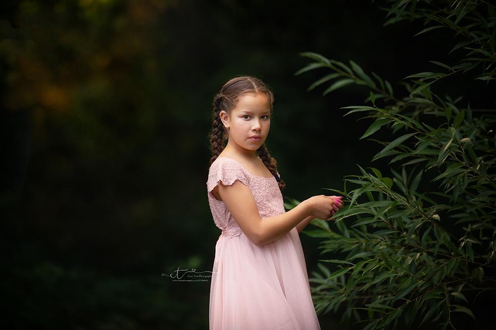 Girl in woodland holding onto leaves at childrens photo shoot Horsham