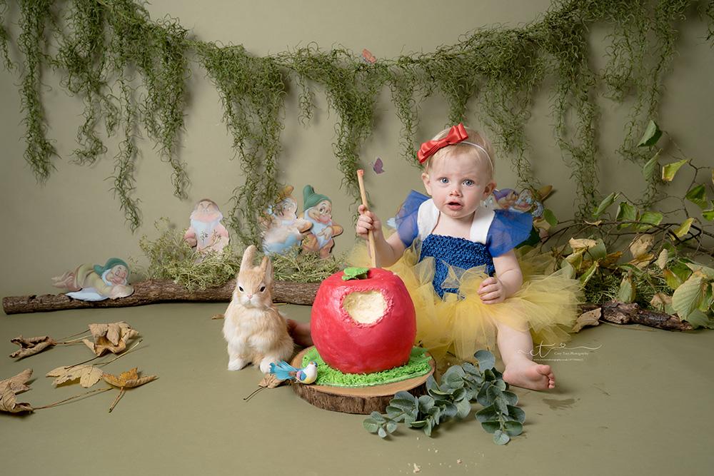 girl holdingwooden spoon at Snow White themed cake smash in Kent