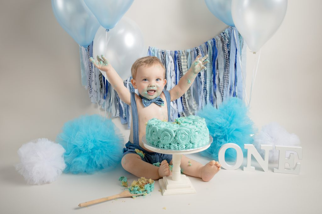 Baby boys waves arms to celebrate his first birthday cake smash in East Grinstead