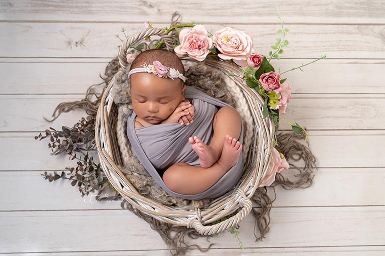 Newborn baby girl laying in wicker basket with flowers at newborn baby photoshoot Crawley